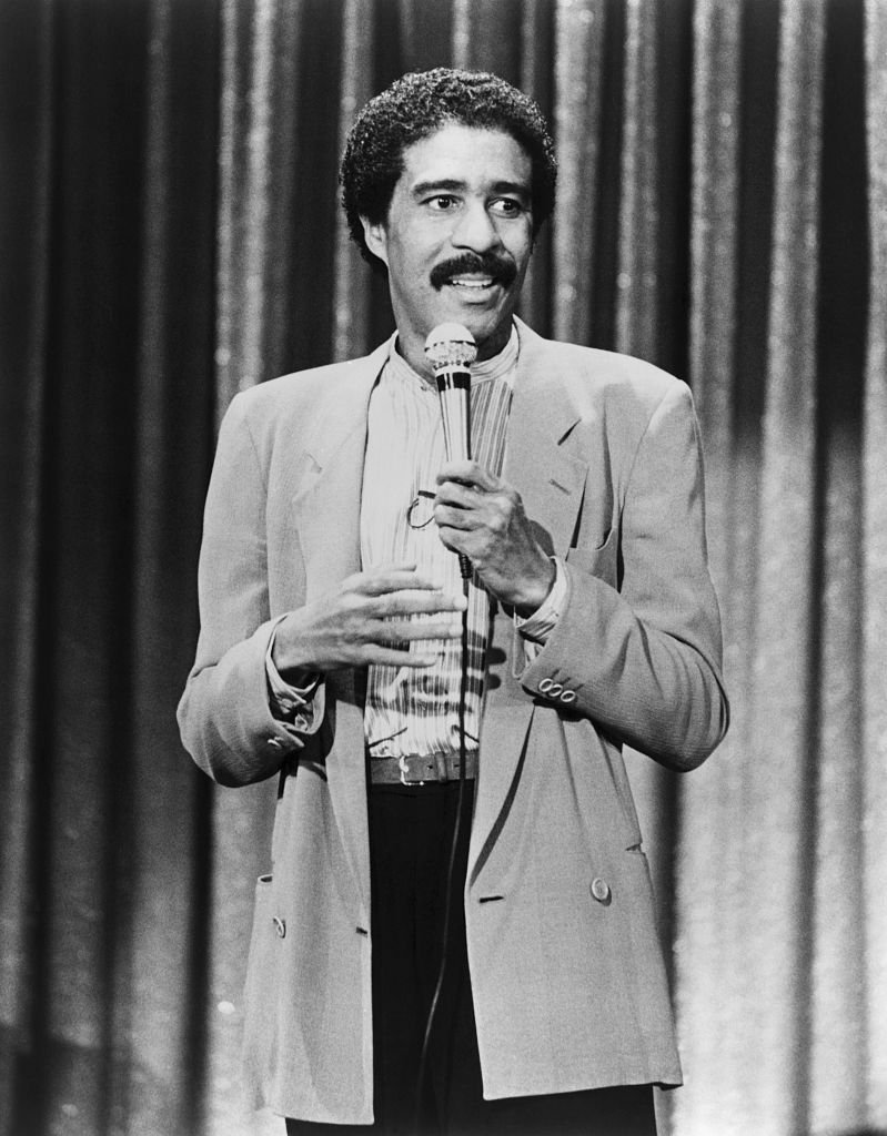 "Image Credits: Getty Images / Bettmann  | Richard Pryor performs his stand-up comedy routine in a scene from his 1982 movie ""Richard Pryor: Live on the Sunset Strip"""