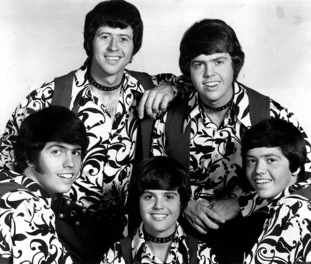 Image Source: Wikimedia Commons/Public Domain/ The Osmonds in 1971 (Clockwise from lower left: Alan, Wayne, Merrill, Jay, Donny)