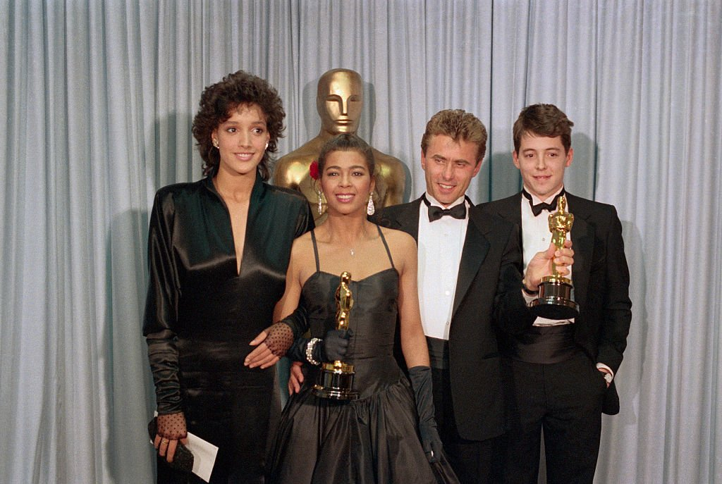 Image Credits: Getty Images / Bettmann | Irene Cara with actress Jennifer Beals, songwriter Keith Forsey, and actor Mathew Broderick.