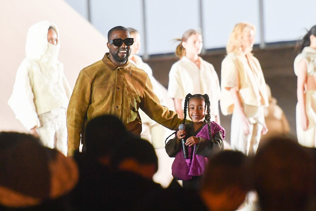 "Image Credit: Getty Images / Kanye West and his daughter North West who sings on the runway during the ""Yeezy Season 8"" show on March 02, 2020 in Paris, France."