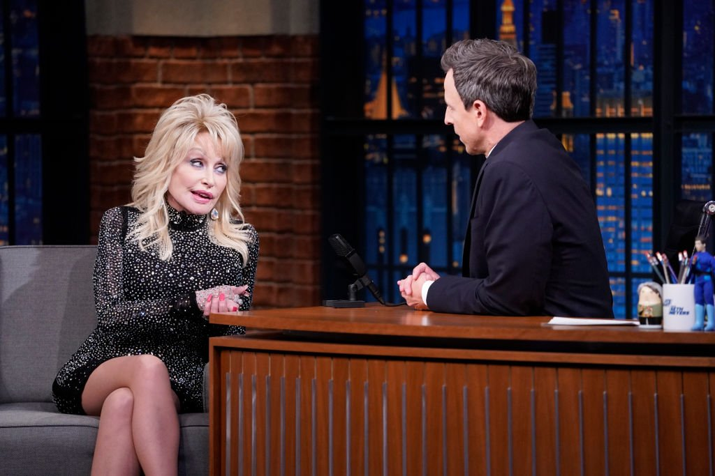 Image Credits: Getty Images / Lloyd Bishop / NBC / NBCU Photo Bank | Singer Dolly Parton during an interview with host Seth Meyers on November 21, 2019.