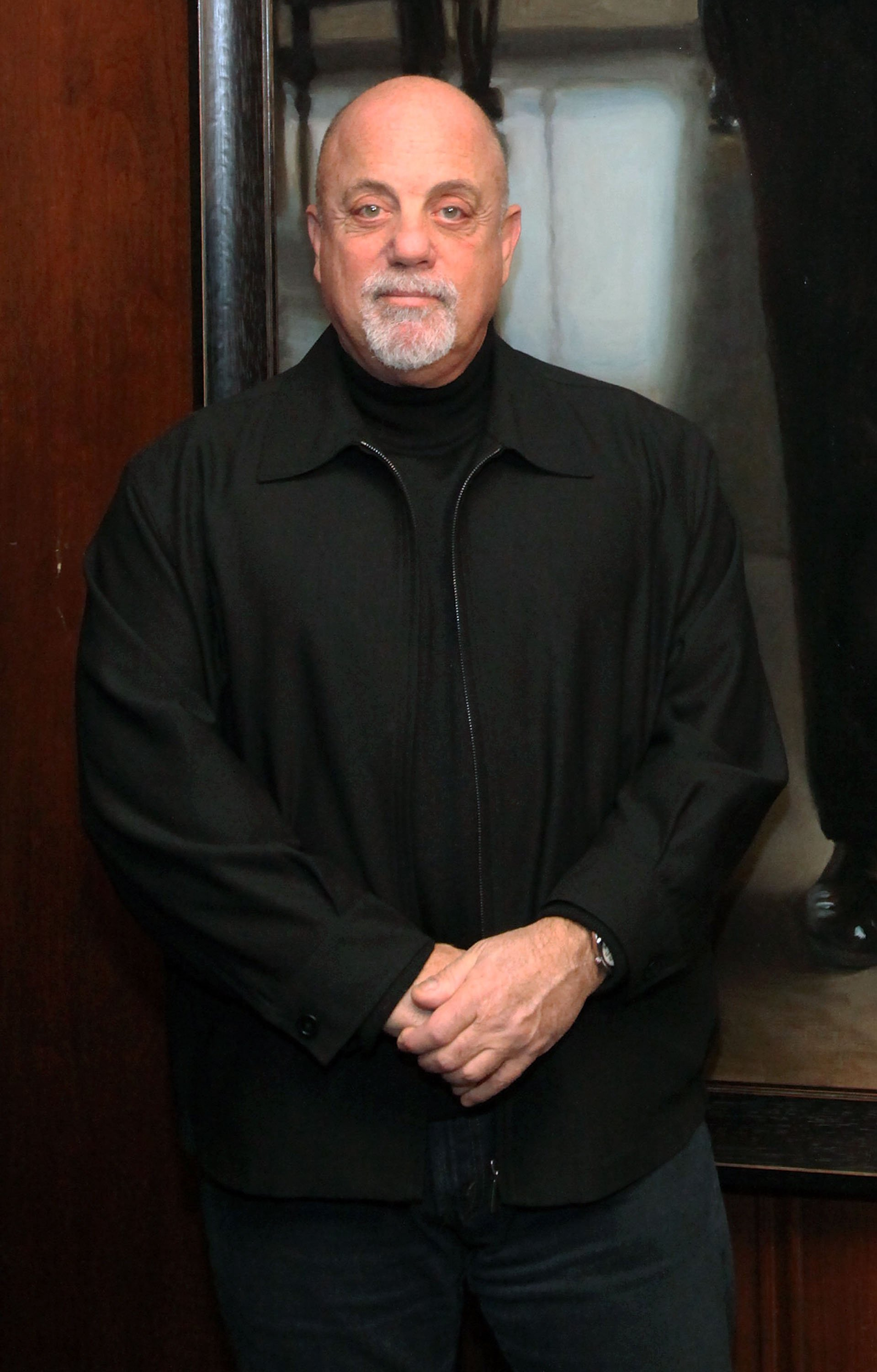 Image Credits: Getty Images / Astrid Stawiarz | Billy Joel stands next to his Steinway Hall Portrait at Steinway Hall on December 12, 2011 in New York City.