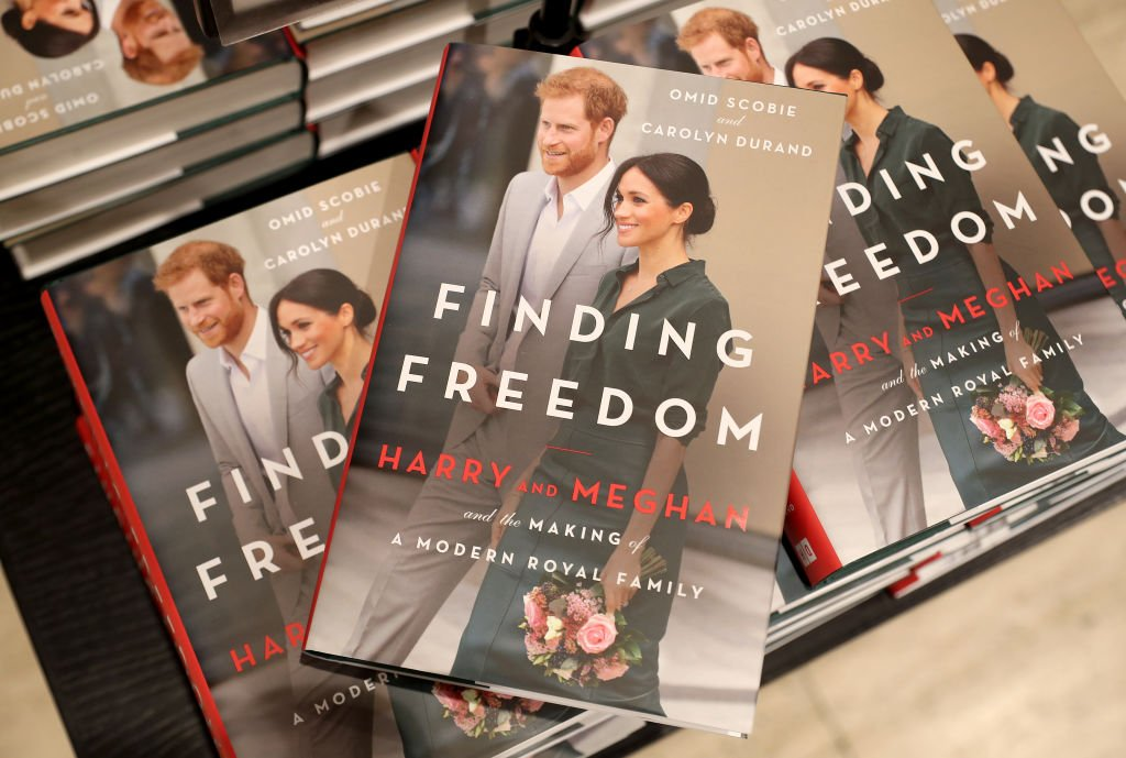 Image Credits: Getty Images | The book about Meghan and Harry, Finding Freedom, is photographed by the media.