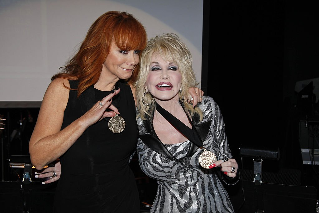 Image Credits: Getty Images / Ed Rode | Reba and  Dolly Parton at the Country Music Hall of Fame celebration