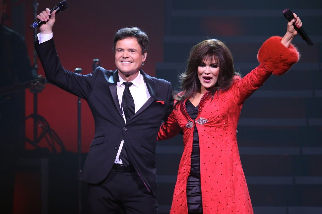 "Image Credit: Getty Images / Entertainers Donny and Marie Osmond are shown performing on stage during a ""live"" holiday concert show on December 27, 2014."