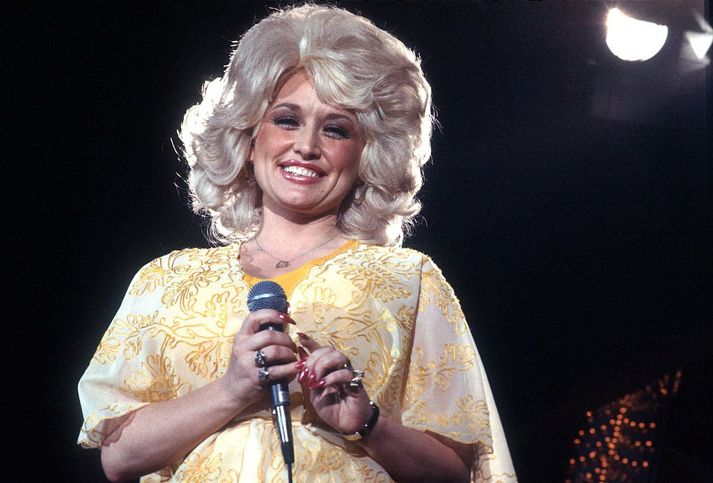 Image Credits: Getty Images / Michael Ochs Archives | Country singer Dolly Parton performs onstage wearing a yellow dress in circa 1975 in Los Angeles, California.