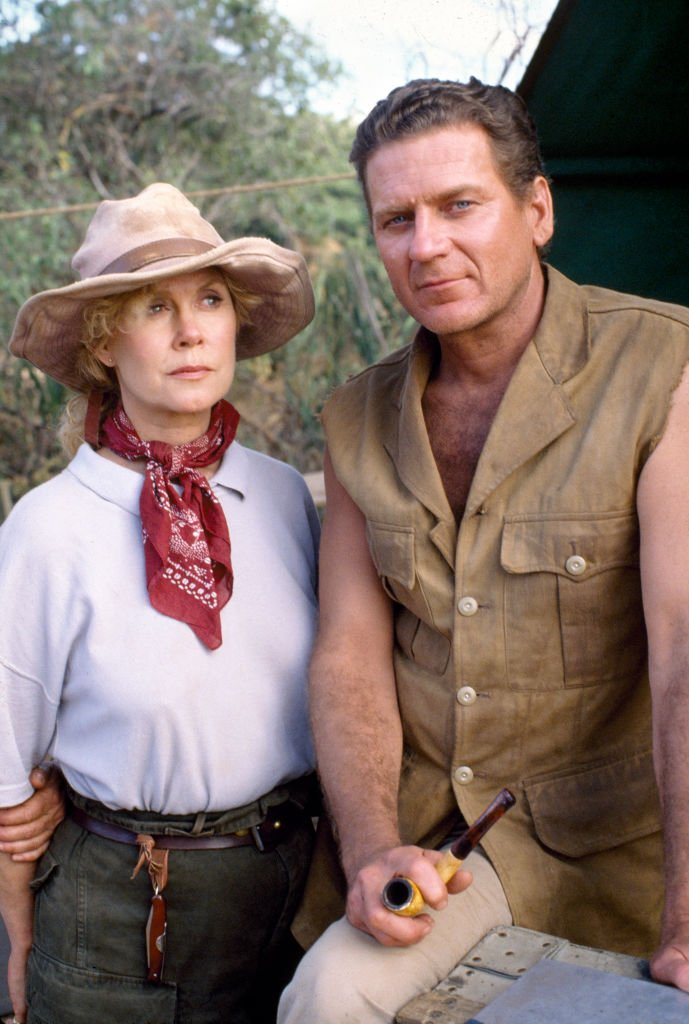 Image Credits: Getty Images / CBS | Face to Face, a made-for-TV movie. A conflict between two professionals, leads to love, amidst challenged tribal traditions in the African savannah. Pictured is Robert Foxworth (as Tobias Williams, miner) and Elizabeth Montgomery (as Dr. Diana Firestone, a paleontologist). Photo dated December 1, 1988. Originally broadcast January 24, 1990. Shot on location in Kenya, Africa.