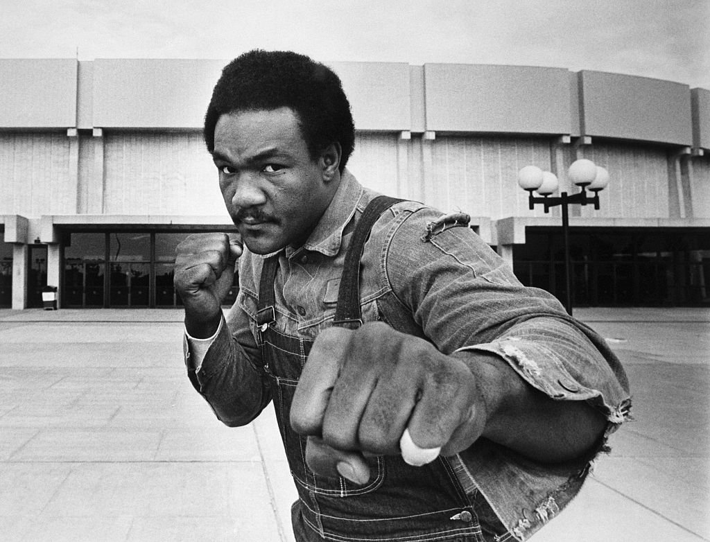 Image Source: Getty Images/Bettmann/Heavyweight contender George Foreman strikes a fighting pose in front of Nassau Coliseum here where he meets Joe Frazier in a 12-round bout