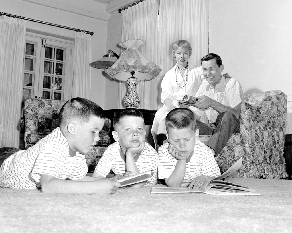 Image Credits: Getty Images / NY Daily News Archive | Johnny Carson and his family at his home, Birch Hill Estate, Winfield Ave, Harrison, N.Y. Cory Carson, 4, is wrapped in his own thoughts as parents relax, brothers Kit (left) and Ricky (right) leaf through picture books.