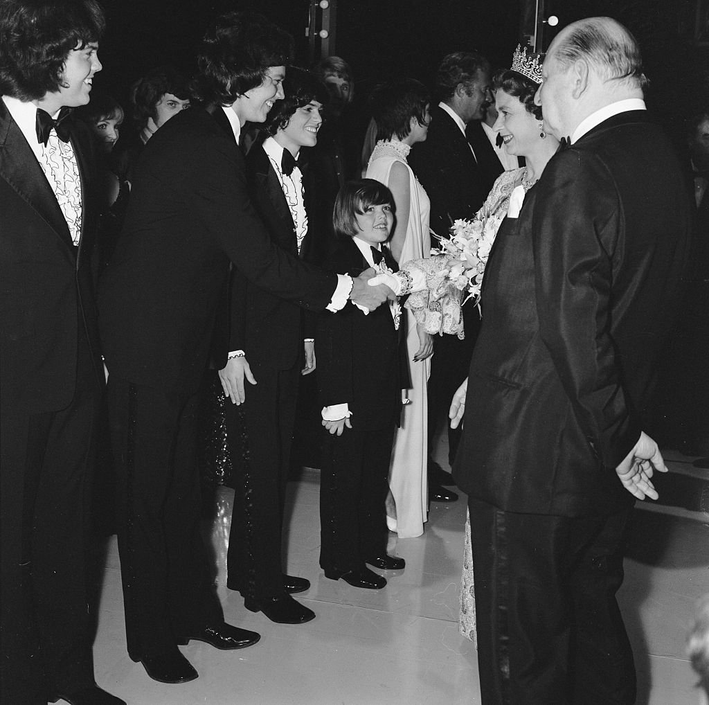 Image Source: Getty Images/MirrorpixHer Majesty Queen Elizabeth II, escorted by Media mogul Lew Grade (right), shakes hands with a member of the Osmonds pop