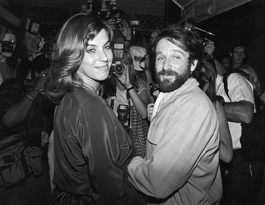 Image Credits: Getty Images / David McGough / DMI / The LIFE Picture Collection | Valerie Velardi and her husband, American comedian and actor Robin Willimas, and a huge number of photographers packed into singer Paul Simon's apartment to celebrate the singer's wedding to actress Carrie Fisher, New York, New York, August 16, 1983.