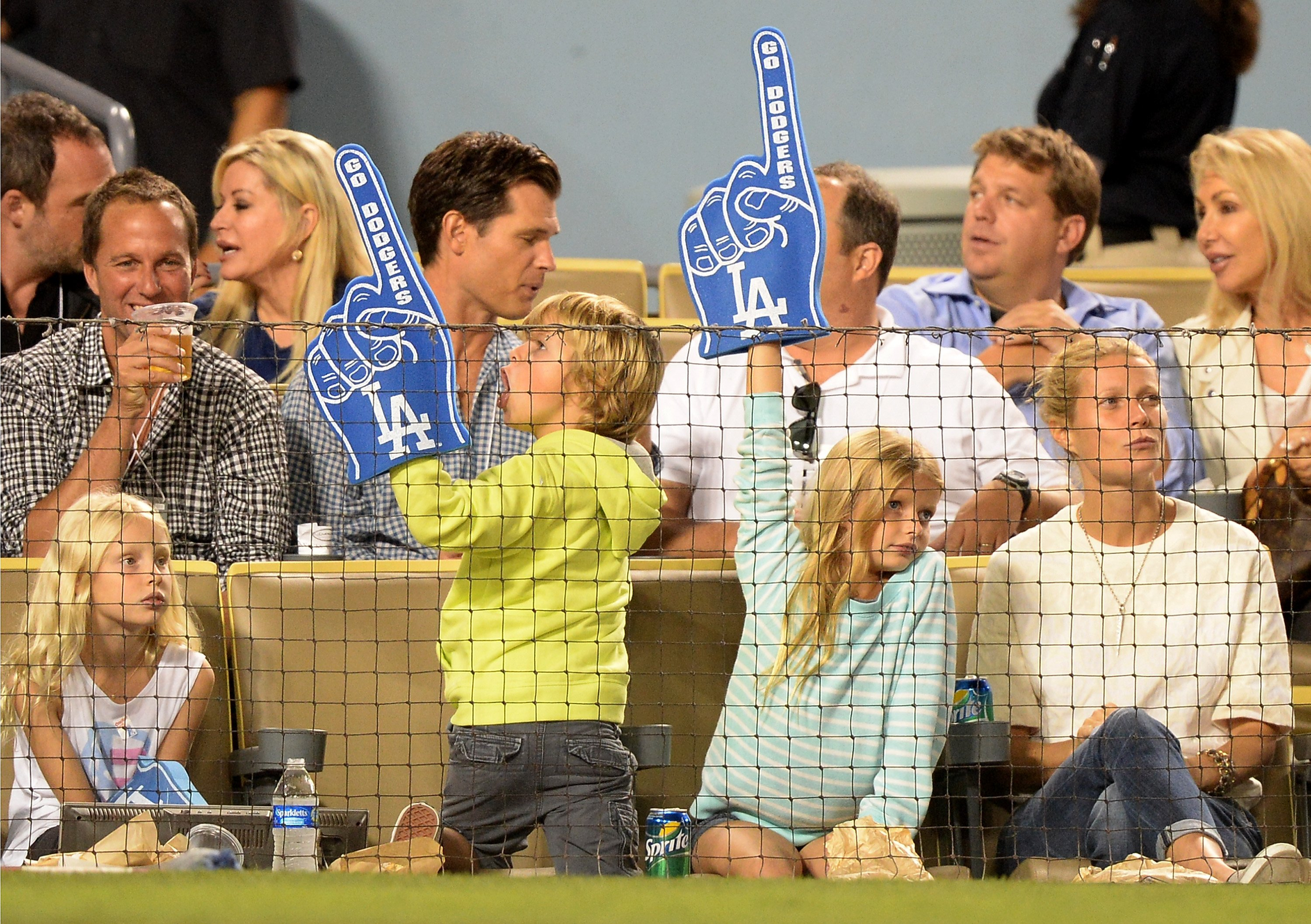 Image Credits: Getty Images / Harry How | Actress Gwyneth Paltrow (R) and Moses Martin and Apple Martin watch the game between the Arizona Diamondbacks and the Los Angeles Dodgers at Dodger Stadium on September 11, 2013 in Los Angeles, California.