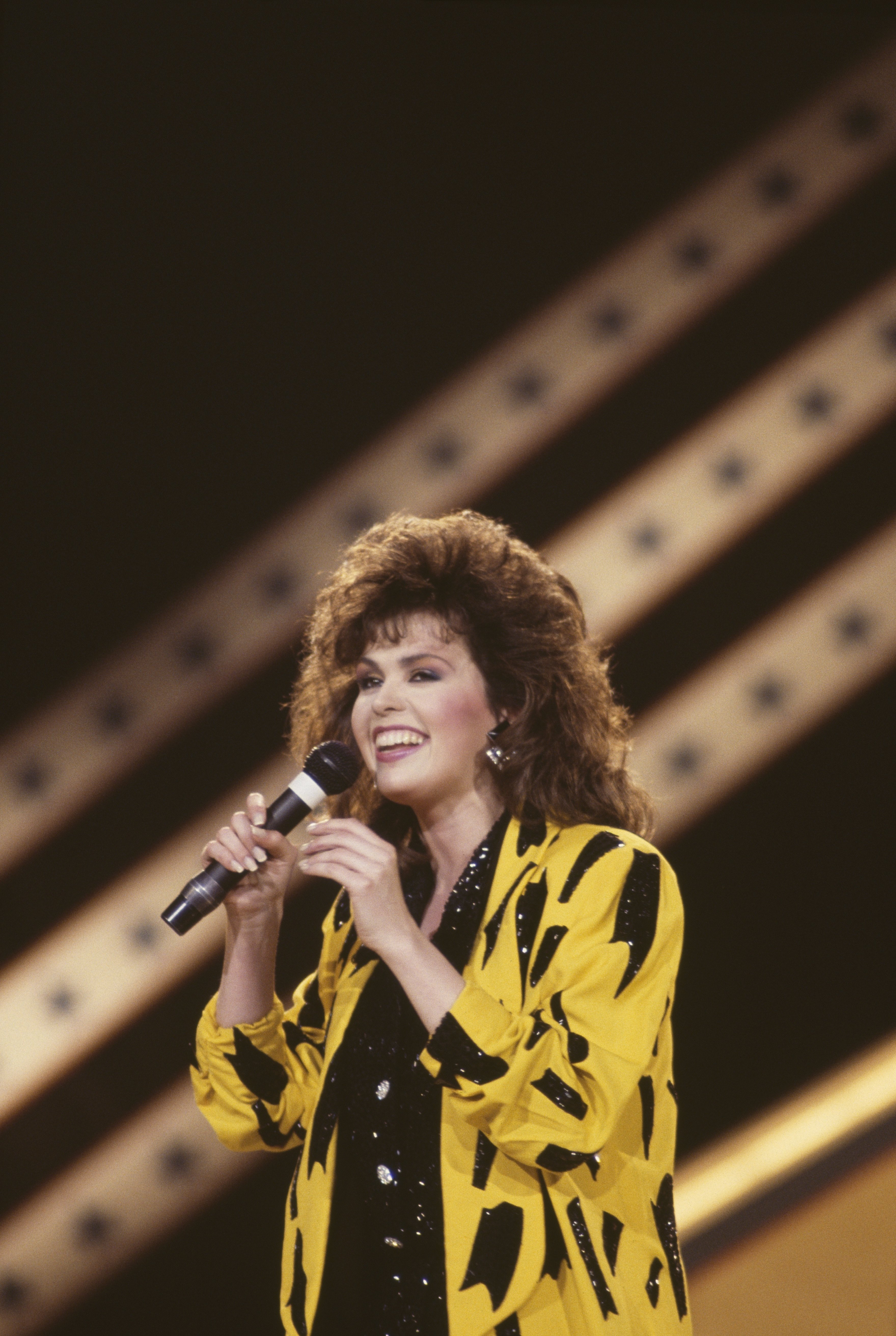 Image Credits: Getty Images / David Redfern / Redferns | Marie Osmond, US singer and musician, singing into a microphone during a live concert performance, on stage at the International Festival of Country Music, held at Wembley Arena, London, England, Great Britain, 1 April 1986.