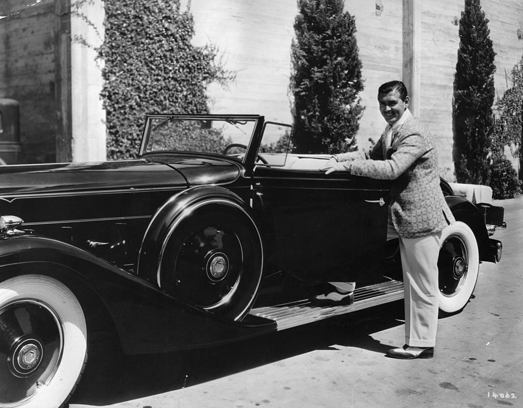 Image Credit: Getty Images / American actor Clark Gable posing with his sports car at the MGM studios.