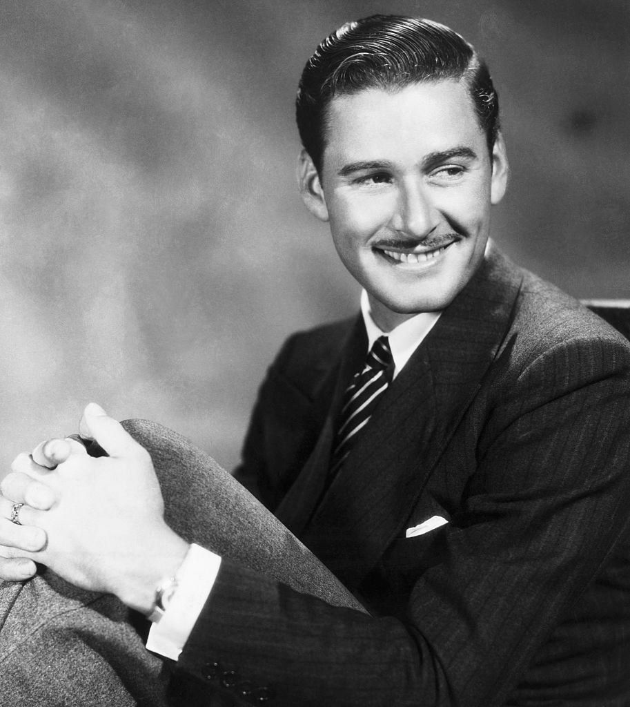 Image Source: Getty Images/Bettmann/Portait of actor Errol Flynn (1909-1959), with his hands around his knees