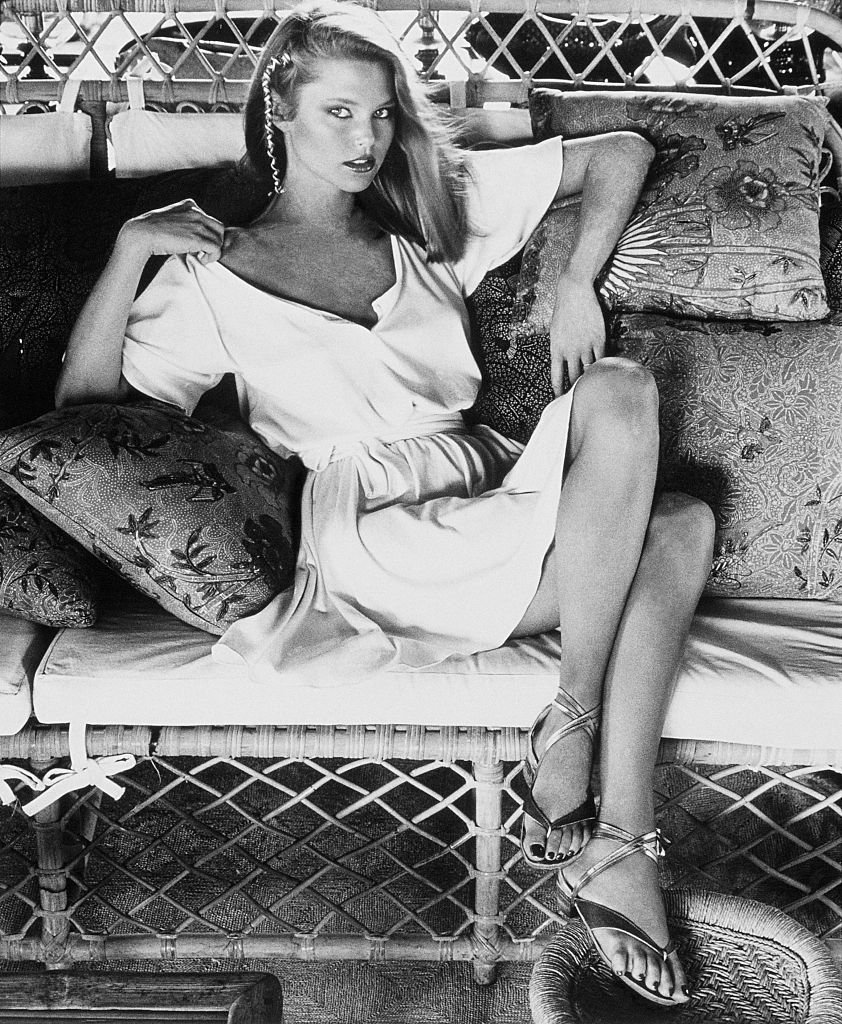 Image Credits: Getty Images / Kourken Pakchanian / Condé Nast | Model Christie Brinkley, sitting with crossed legs on a wicker couch with pillows, and wearing a short ivory T-shirt dress by Callaghan.