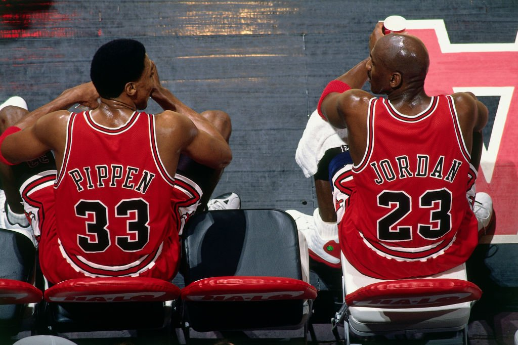 Image Credits: Getty Images / Andy Hayt / NBAE | Scottie Pippen #33 and Michael Jordan #23 of the Chicago Bulls sit on the bench during the game against the Vancouver Grizzlies at General Motors Place on January 27, 1998 in Vancouver, British Columbia, Canada.
