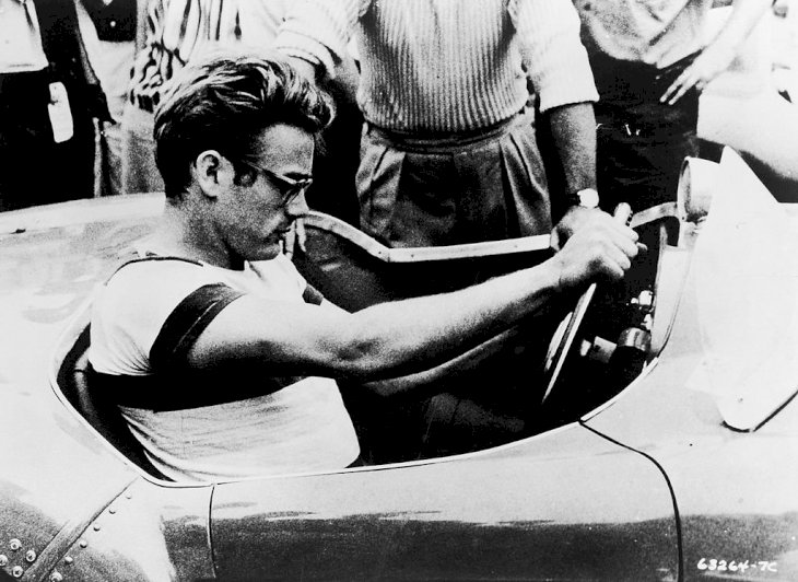 Image Credit: Getty Images/Warner Bros. courtesy of Getty Images | James Dean sits behind the wheel of a sportscar