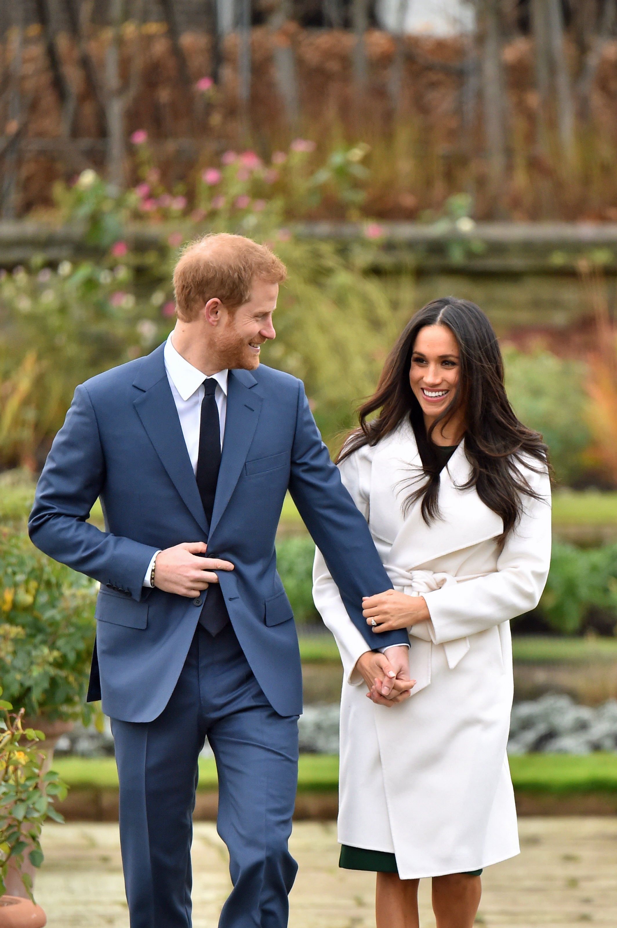 Image Credits: Getty Images / Dominic Lipinski / PA Images | Prince Harry and Meghan Markle in the Sunken Garden at Kensington Palace, London, after the announcement of their engagement.