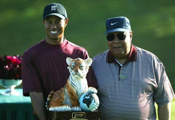 Image Credits: Getty Images / Doug Benc | Tiger Woods (L) stands with his father, Earl Woods, during the trophy presentation of the Target World Challenge on December 12, 2004 at Sherwood Country Club in Thousand Oaks, California. Woods won the event at 16 under par.