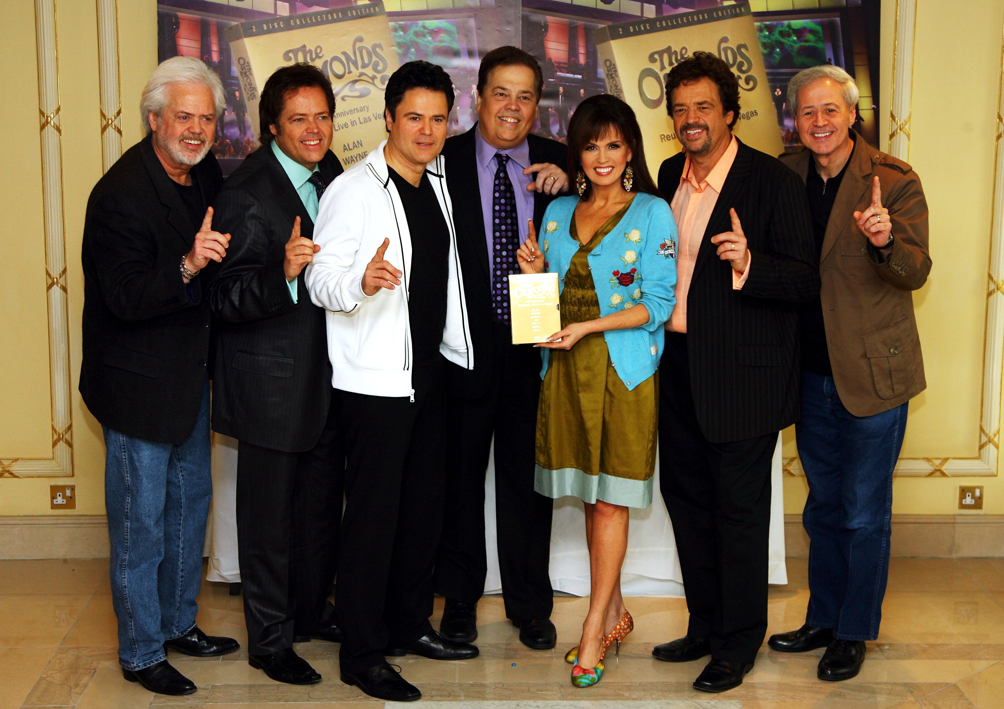 Image Credits: Getty Images / Chris Jackson | The Osmonds (L-R) Merril, Jimmy, Donny, Alan, Marie, Jay and Wayne pose for a photograph at a photocall promoting their number one DVD and 50th Anniversary Concert in Las Vegas at the Millenium Hotel on May 29, 2008 in London, England.