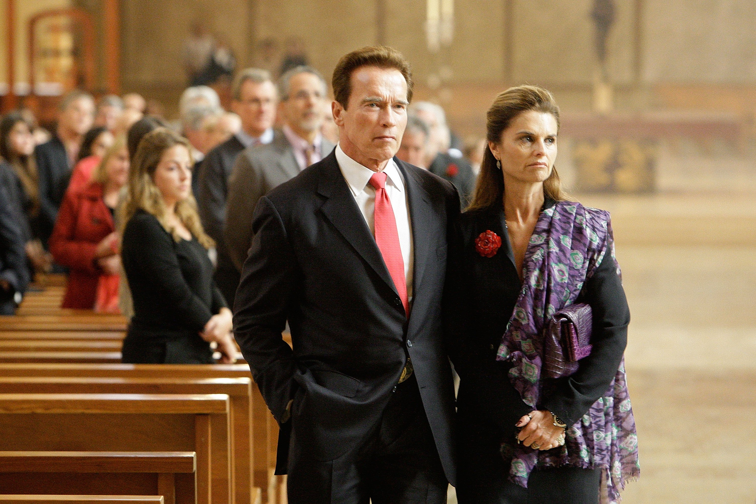 Image Credits: Getty Images / Reed Saxon-Pool | California Governor Arnold Schwarzenegger and wife Maria Shriver attend the funeral Mass for Italian film mogul and Hollywood producer Dino De Laurentiis at the Cathedral of Our Lady of the Angels on November 15, 2010 in Los Angeles, California.