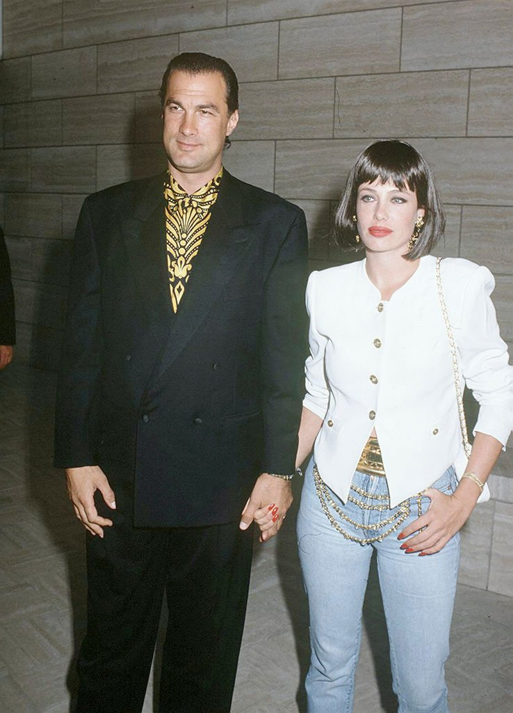 Image Credits: Getty Images / Kypros | American actor, film producer, screenwriter, martial artist, and musician Steven Seagal with his wife, American-born English actress and model Kelly LeBrock, circa 1990