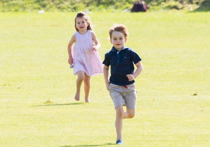 Image Credit: Getty Images / Prince George of Cambridge and Princess Charlotte of Cambridge run together during the Maserati Royal Charity Polo.