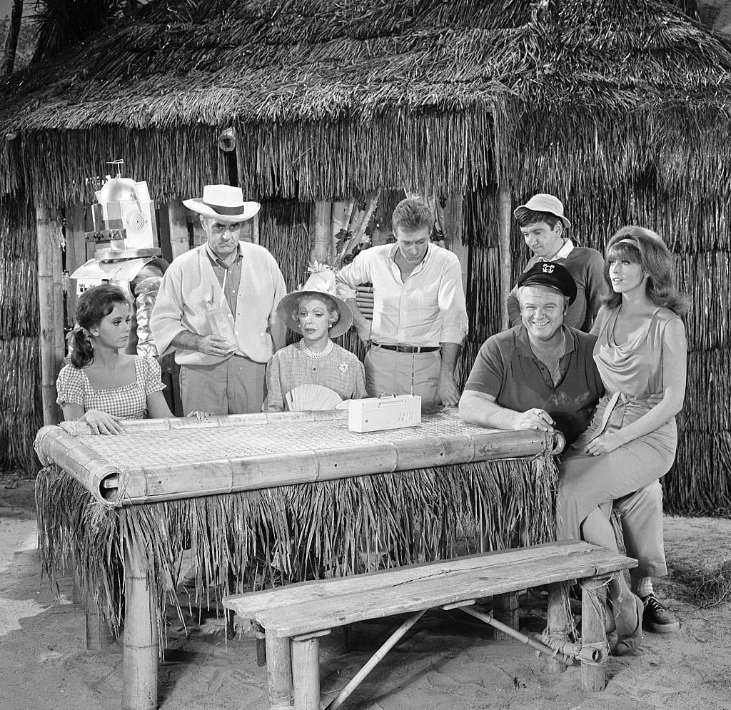 "Image Credit: Getty Images / NOVEMBER 18: Gilligan's Island cast members, from left, Dawn Wells (as Mary Ann Summers), Jim Backus (as Thurston Howell III), Natalie Schafer (as Mrs. Lovey Howell), Russell Johnson (as Professor Roy Hinkley), Alan Hale, Jr. (as The Skipper Jonas Grumby, seated), Bob Denver (as Gilligan) and Tina Louise (as Ginger Grant) appearing in episode: ""Gilligan's Living Doll."""