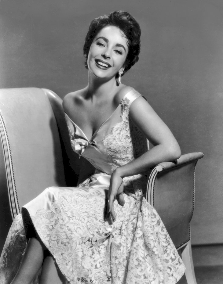 Image Credit: Getty Images/Hulton Archive | Elizabeth Taylor seated, wearing a sleeveless lace brocade dress.