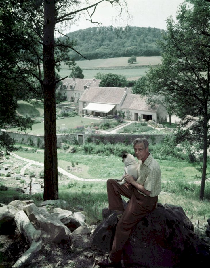 Image Credits: Getty Images / Frank Scherschel / The LIFE Picture Collection | Photograph of Edward VIII, the Duke of Windor (1894 - 1972), as he sits on a large rock on a hillside above his home, la Moulin de la Tuilerie, outside of Paris, France, 1955.