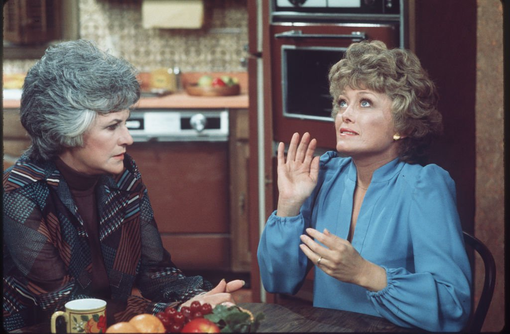 Image Credits: Getty Images / CBS Photo Archive | American actresses Beatrice Arthur (as Maude Findlay) (left) and Rue McClanahan (as Vivian Cavender Harmon) talk at a table in a scene from the television show 'Maude,' Los Angeles, California, mid 1970s.