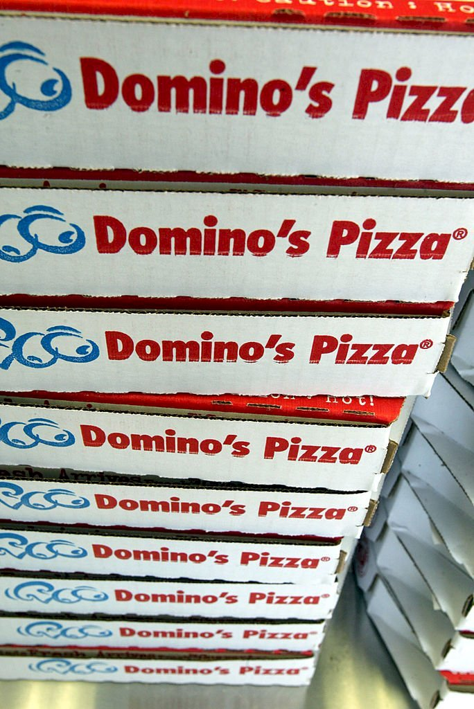 Image Credits: Getty Images / Joe Raedle | Stack of Domino's Pizza boxes.