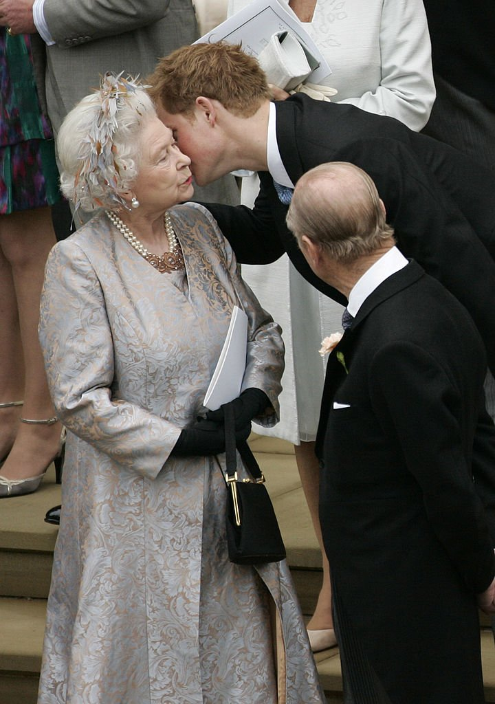 Image Credits: Getty Images / POOL / Tim Graham Picture Library   Prince Harry kisses his grandmother Queen Elizabeth II after the wedding of Peter Phillips to Autumn Kelly, at St George's Chapel in Windsor Castle on May 17, 2008 in Windsor, England.