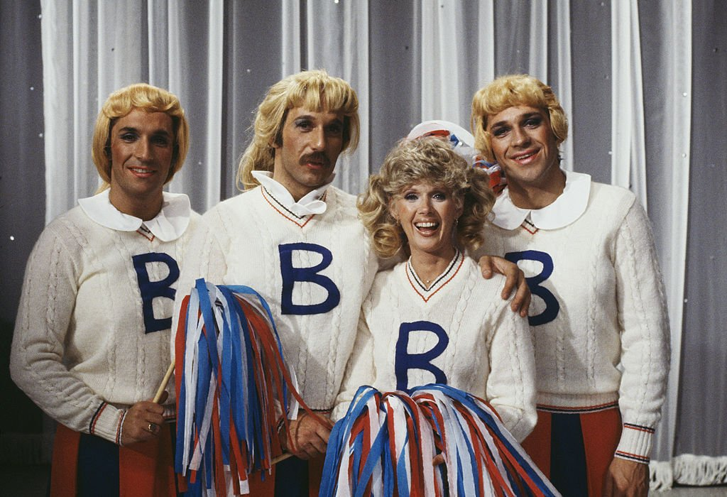 Image Credits: Getty Images / Richard Blanshard | The Hudson Brothers, Bill Hudson, Brett Hudson and Mark Hudson, dressed as cheerleaders for a sketch in the television comedy show 'Bonkers!', 1979.