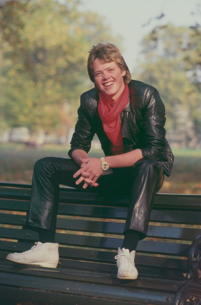 Image Credits: Getty Images / Michael Putland | Jimmy Osmond, American singer and member of American family group The Osmonds, posed wearing a leather jacket and trousers as he sits on a bench in a park in London in October 1983.