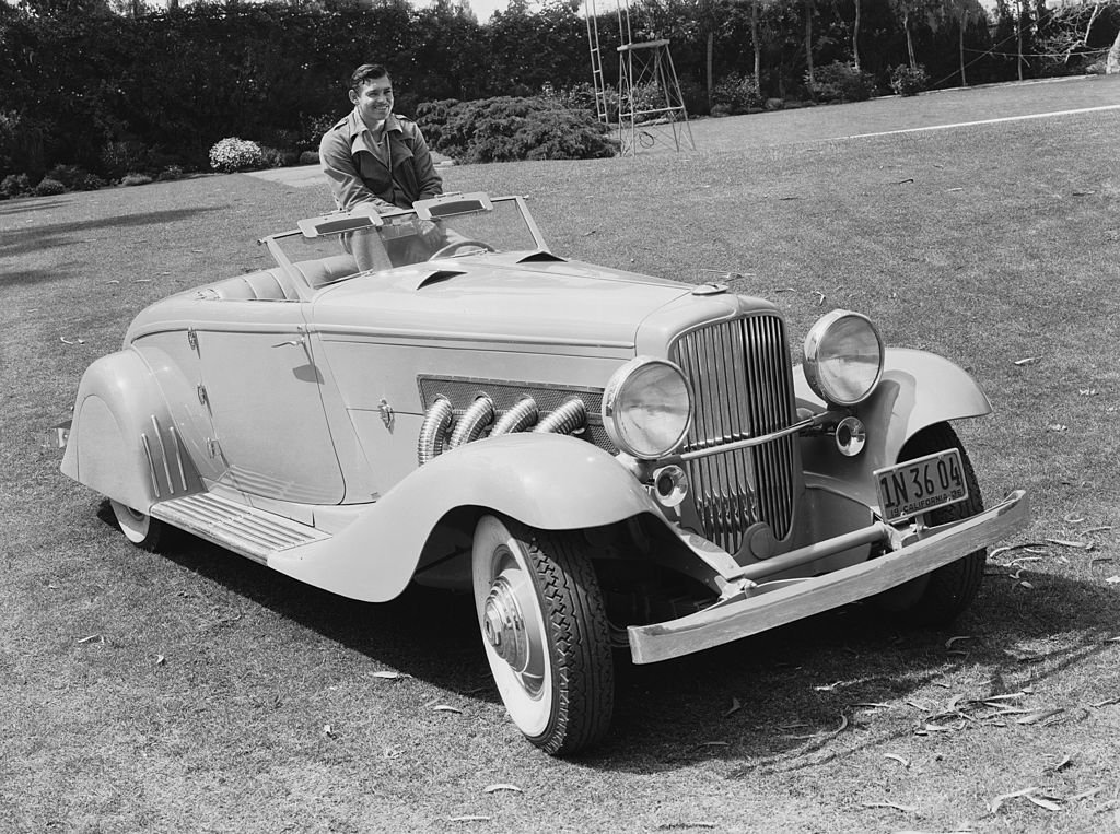 Image Credit: Getty Images / American screen star Clark Gable known as the 'King of Hollywood', poses in his custom-bodied Duesenberg J roadster.
