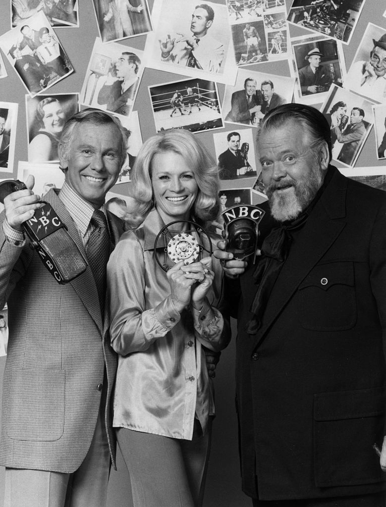 Image Credits: Getty Images / Hulton Archive | American television talk show host Johnny Carson, American actor Angie Dickinson and American film director and actor Orson Welles hold vintage NBC microphones and smile as they stand in front of a wall plastered with photographs of celebrities.