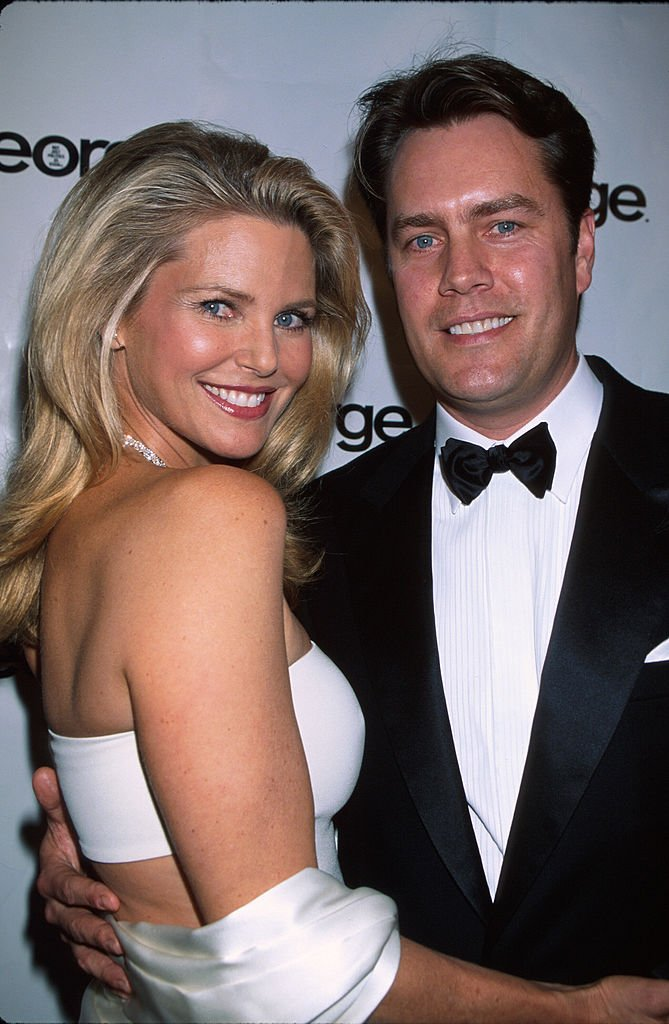 Image Credits: Getty Images / Dave Allocca / DMI / The LIFE Picture Collection | Model Christie Brinkley and husband, architect Peter Cook, at party for television series The West Wing.