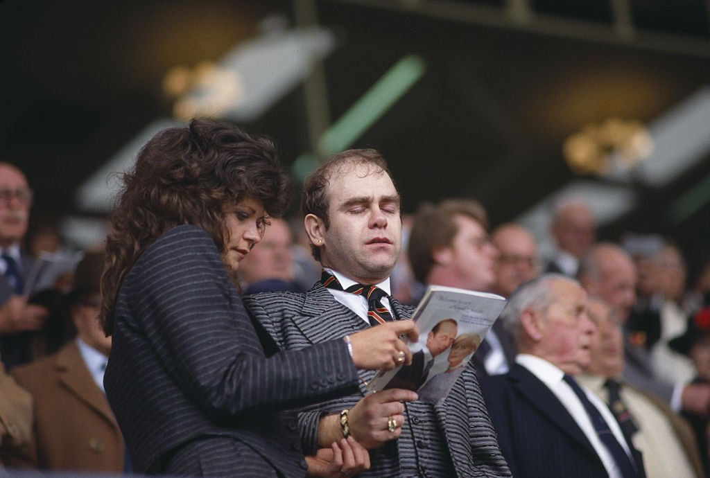 Image Credit: Getty Images / Elton John singing the Cup Final Hymn with his wife Renate Blauel at Wembley Stadium before the FA Cup Final in 1984.