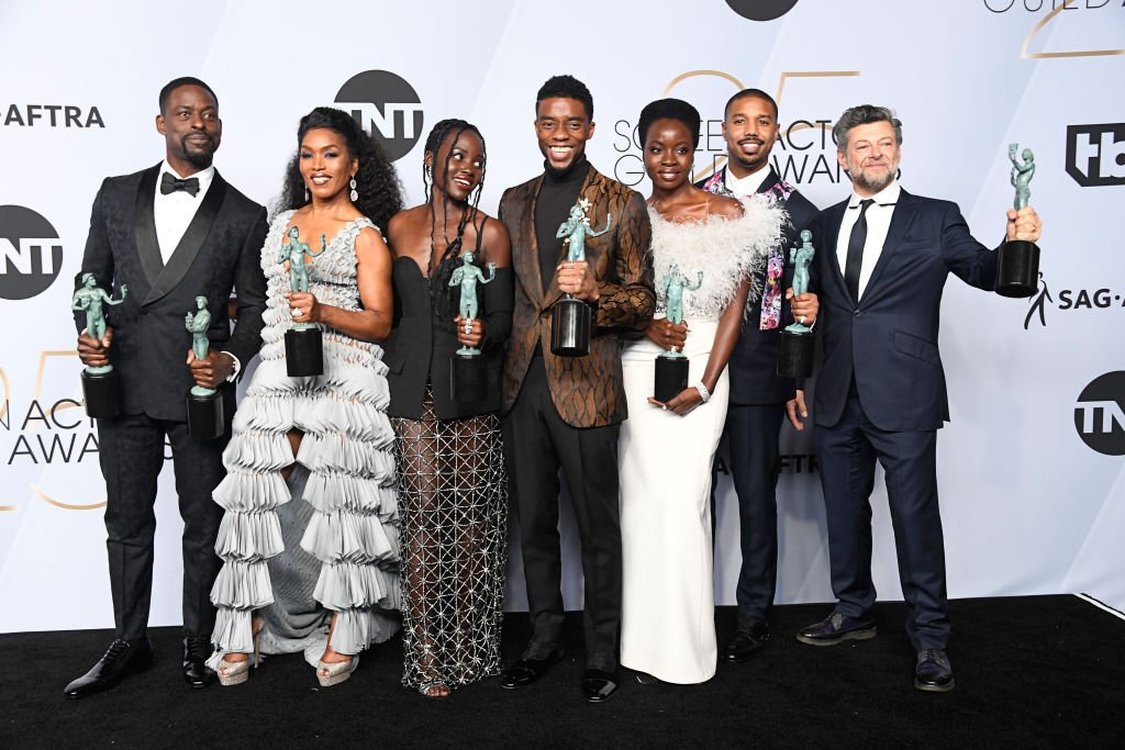 Image Credits: Getty Images / Frazer Harrison | (L-R) Sterling K. Brown, winner of Outstanding Performance by a Cast in a Motion Picture for 'Black Panther' and Outstanding Performance by an Ensemble in a Drama Series for 'This Is Us;' Angela Bassett, Lupita Nyong'o, Chadwick Boseman, Danai Gurira, Michael B. Jordan, and Andy Serkis, winners of Outstanding Performance by a Cast in a Motion Picture for 'Black Panther,' pose in the press room during the 25th Annual Screen Actors Guild Awards at The Shrine Auditorium on January 27, 2019 in Los Angeles, California.