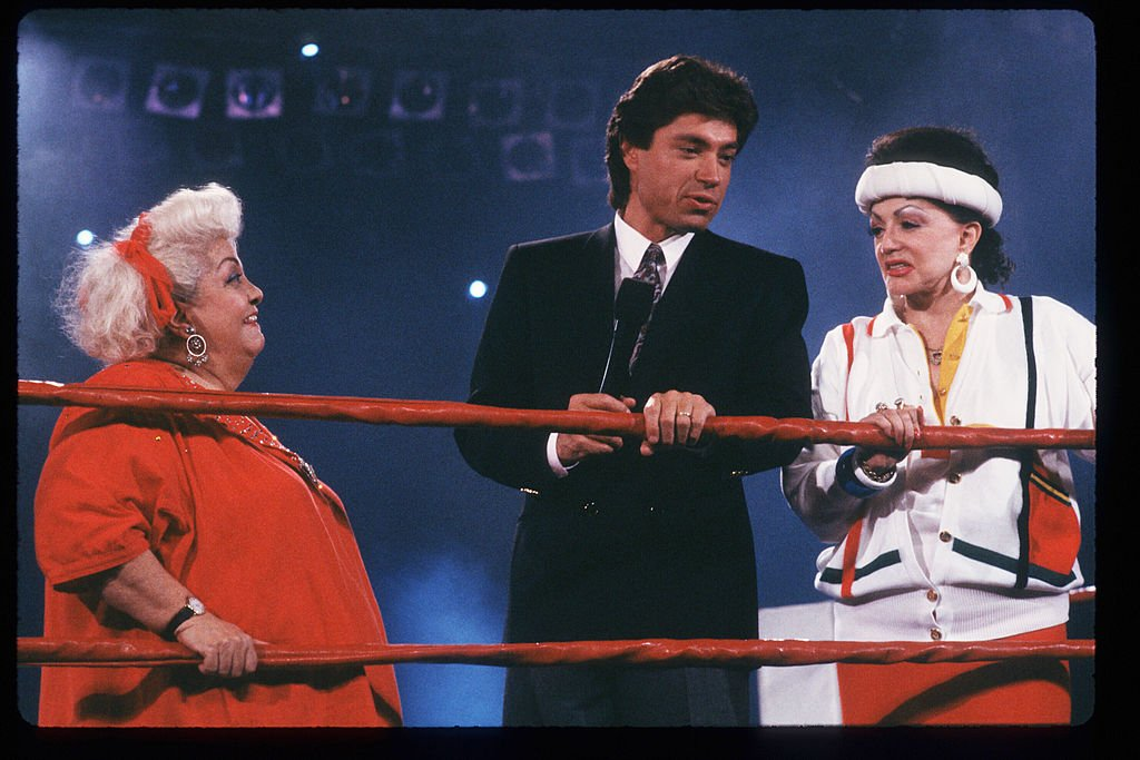 "Image Credits: Getty Images / Laura Luongo / Liaison | ""Late Show"" host Ross Shaffer speaks with Jacqueline Stallone in the ring May 4, 1988 in Los Angeles, CA. Jacqueline Stallone manages the all-female wrestling team GLOW Girls (Gorgeous Ladies Of Wrestling) which has achieved fame through their use of colorful costumes and elegant acrobatics."