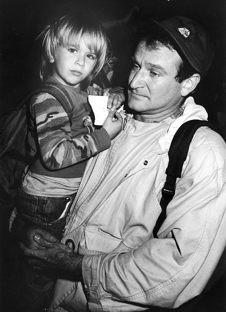 Image Credits: Getty Images / Kevin Winter / DMI / The LIFE Picture Collection | American comedian Robin Williams holds his son Zachary at the Comic Relief '87 charity event, Los Angeles, California, Novemeber 14, 1987.