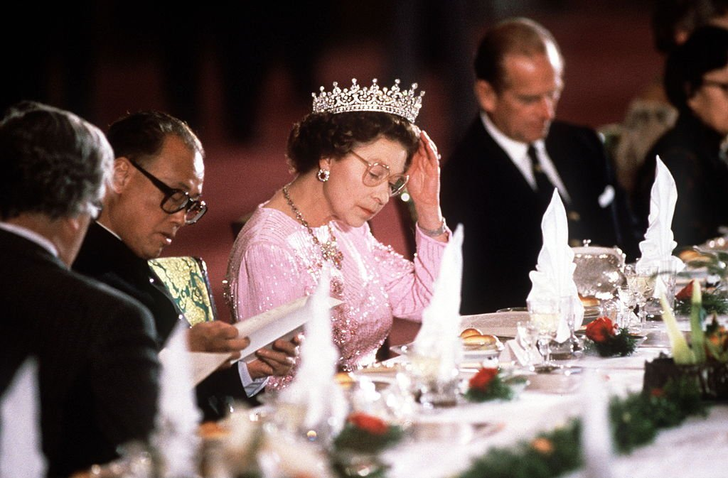Image Credit: Getty Images / The Queen Adjusting Her Tiara During Her Visit With Prince Philip To Peking, China.