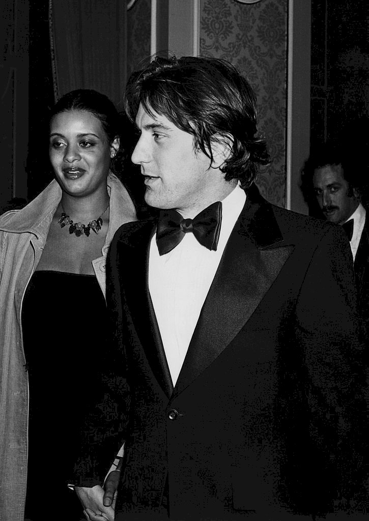 Image Credits: Getty Images / Michael Ochs Archive | Diahnne Abbott and Robert De Niro arrive at the 5th Annual AFI Lifetime Achievement Award, Salute to Bette Davis on March 1, 1977, in Hollywood, California.