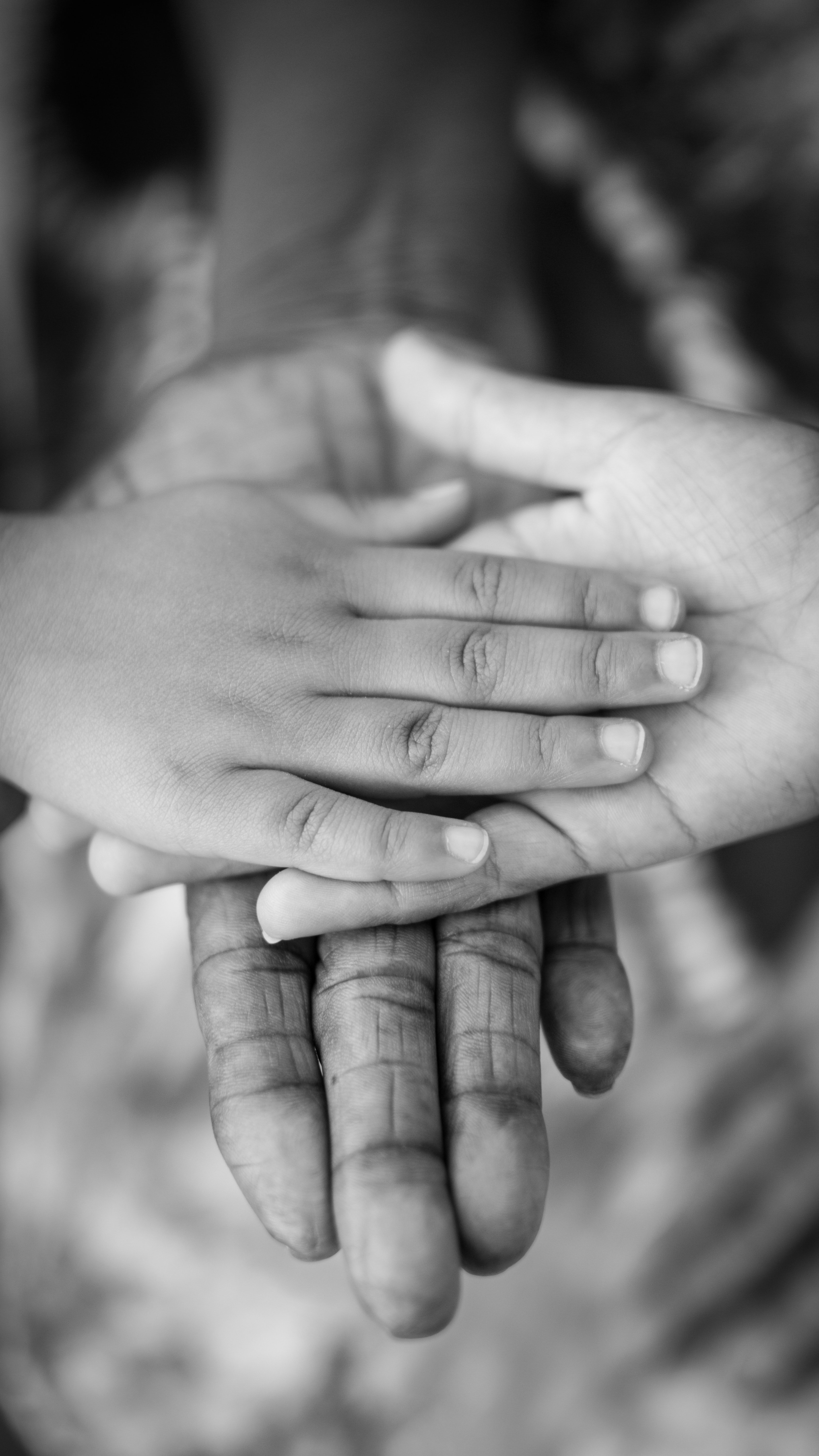 A child's hand on top of adult hands | Pexels
