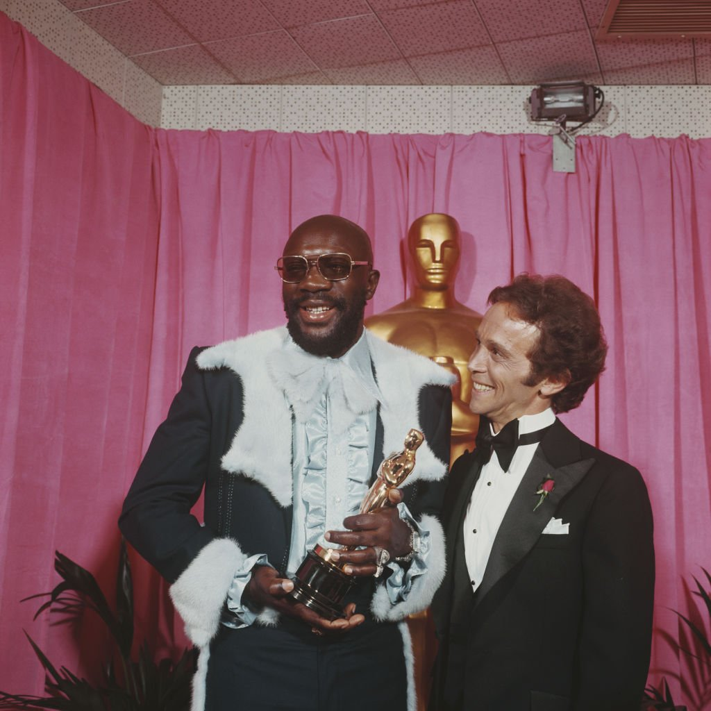 Image Credits: Getty Images / Rolls Press/Popperfoto  | American musician and actor Isaac Hayes pictured holding his Oscar statuette Academy Award with actor Joel Grey