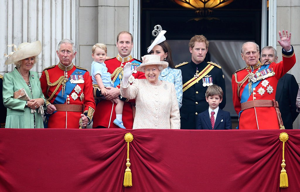 Image Credits: Getty Images / Chris Jackson | (L-R) Camilla, Duchess of Cornwall, Prince Charles, Prince of Wales, Prince George of Cambridge, Prince William, Duke of Cambridge, Catherine, Duchess of Cambridge, Queen Elizabeth II, Prince Harry and Prince Philip, Duke of Edinburgh (R) watch the fly-past from the balcony of Buckingham Palace following the Trooping The Colour ceremony on June 13, 2015 in London, England. The ceremony is Queen Elizabeth II's annual birthday parade and dates back to the time of Charles II in the 17th Century, when the Colours of a regiment were used as a rallying point in battle.