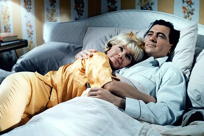 Image Credits: Getty Images / Universal | Doris Day lies in the arms of Rock Hudson in a scene from the film 'Send Me No Flowers', 1964.