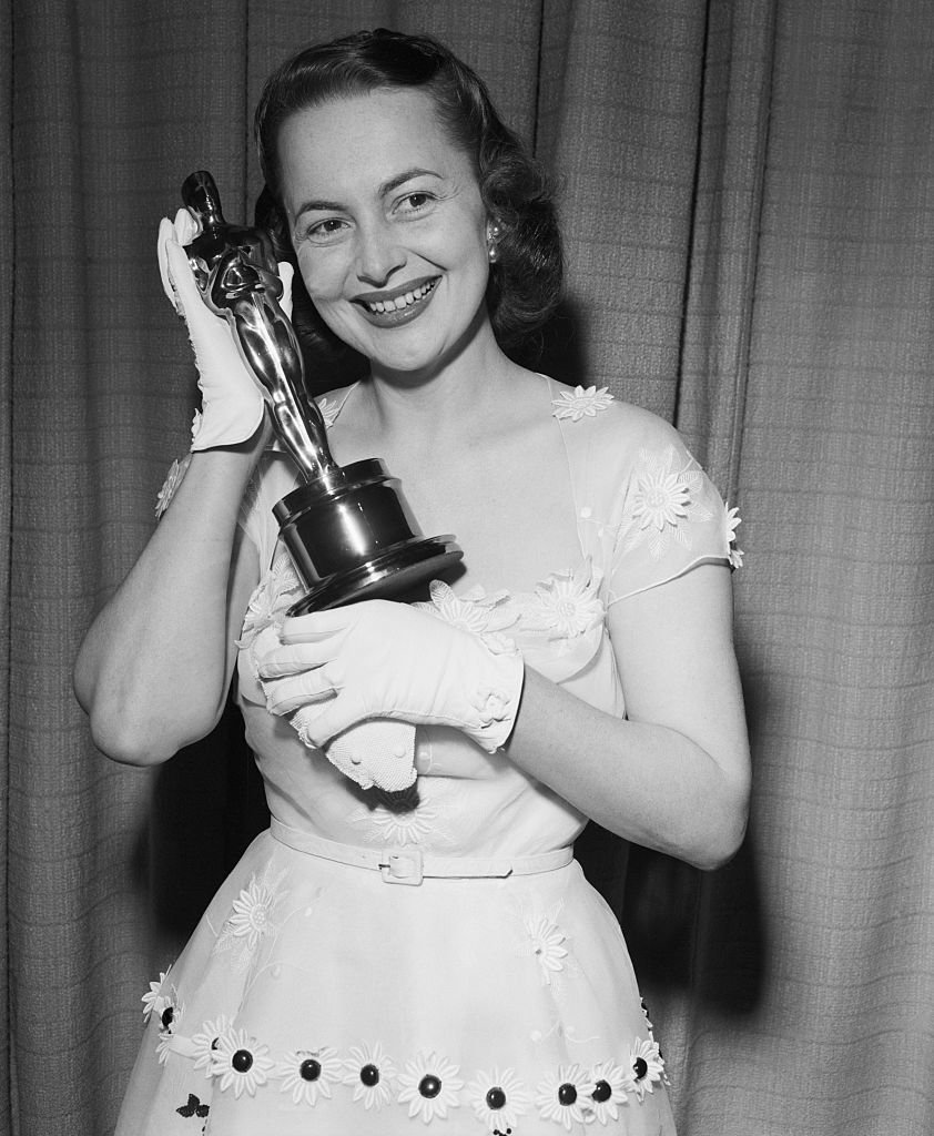 "Image Credits: Getty Images /  Bettmann | Olivia De Havilland proudly displays her second ""Oscar,"" awarded for her performance as the Best Actress of 1949"